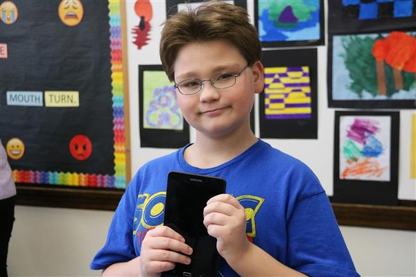 Male student holds electronic device in front of a bulletin board.