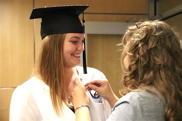 Dental Assisting instructor Melanie Kerschner places a pin on graduate Emily Simpson's jacket