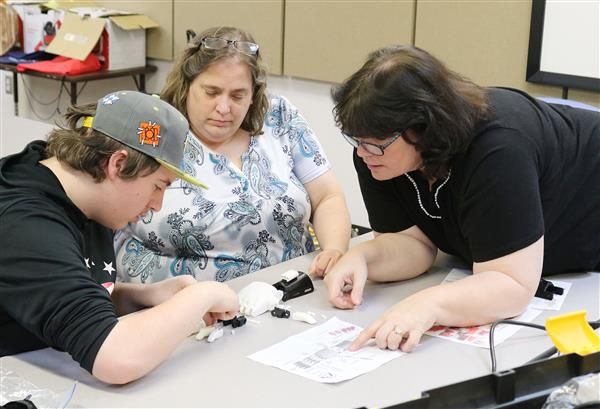 Pictured is a the Oswego County e-NABLE team working to assemble a 3D printed hand.