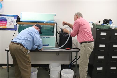 Paul Miller and Jim Rozwood from the Fish Creek Atlantic Salmon Club set up the tank inside Angela Wheeler's classroom at CiT