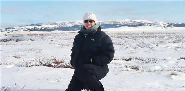 Melanie Kerschner stands in front of the Alaskan tundra during her time working there.